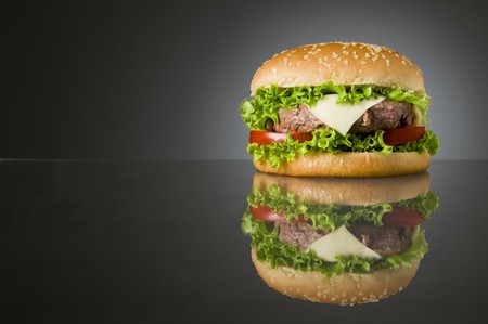 Big fresh delicious homemade hamburger with reflection and space for text photo