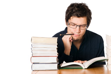 Handsome pensive young man studying on a stack of books on table with a pencil in his mouth photo