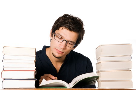 between: Handsome young man studying and reading between stacks of books on table.