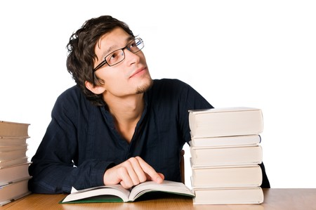 Handsome young man studying and dreaming between stacks of books on table. photo