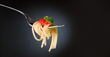 restaurante italiano: Pasta de espaguetis con tomate y albahaca en la horquilla. Comida italiana. Espacio para texto. Imagen de estudio profesional