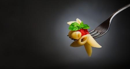 tallarin: Pasta de macarrones con tomate y albahaca en la horquilla. Comida italiana. Espacio para texto. Imagen de estudio profesional