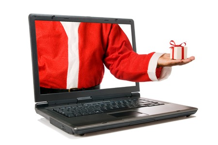 Santa Claus hand with a gift come out from a screen of a laptop computer isolated on white background.