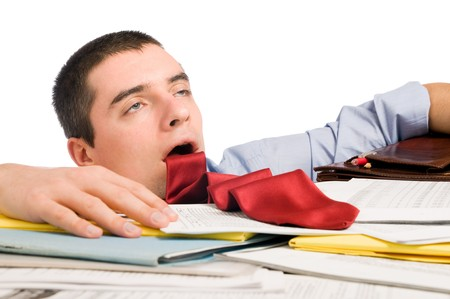 exhausted: Young exhausted businessman with his necktie like a sticked out tongue lying down heap of documents. Stock Photo