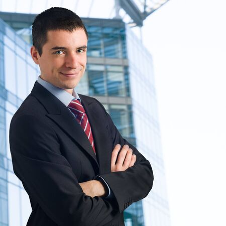 Portrait of young confident businessman against new modern blue office building photo