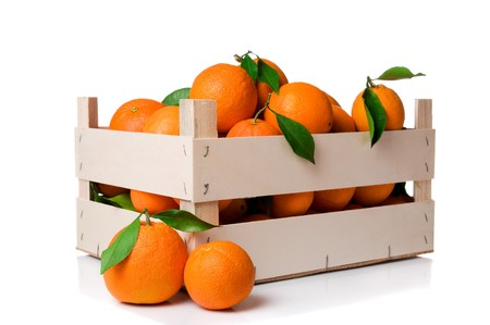 Fresh and ripe orange fruits with leaves in a wooden crate isolated on white background Stock Photo