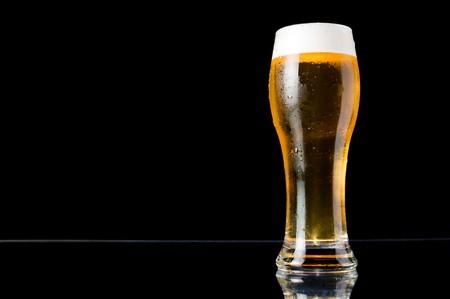 Kaltes Bier mit Wasser Tropfen auf schwarzem Hintergrund