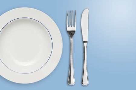 knife and fork: Clean placed plate with fork and knife with copy space on the right.