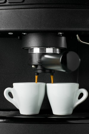 maker: Coffee maker pouring hot espresso coffee in two cups. Take your break!