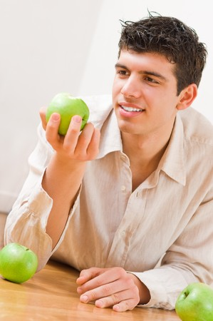 Young man eating green and healthy apples photo