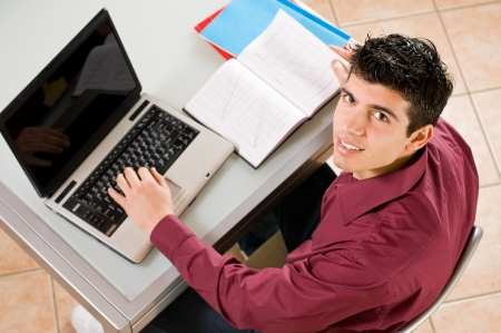 Young man studying and working on his laptop with note pad. photo