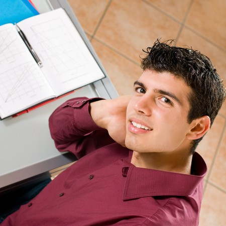 Young man studying and smiling at camera with note pad in the background.