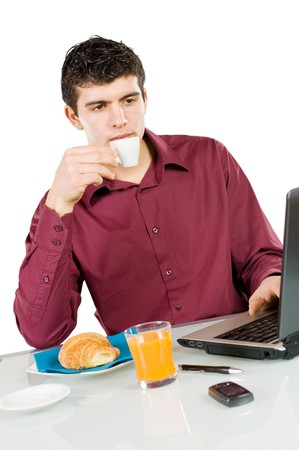 Young busy man studying and working on his laptop while having breakfast isolated on white background photo