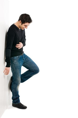 Full length portrait of young laughing man standing against white wall with copy space for your text photo