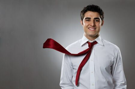 Young businessman smiling at camera with blowing necktie. Good business in action! photo