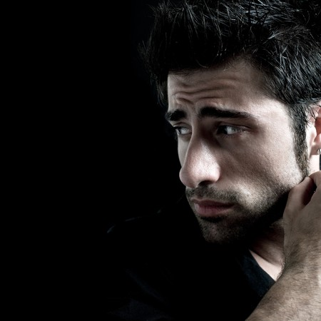 depressed person: Sad and worried latin man looking away