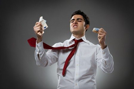curse: Young businessman getting mad with blowing necktie and his bunch of money. Recession and crisis concept!
