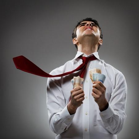 dinero euros: Maldici�n de joven empresario en el destino con corbata y mont�n de dinero. Concepto de recesi�n y crisis!  Foto de archivo