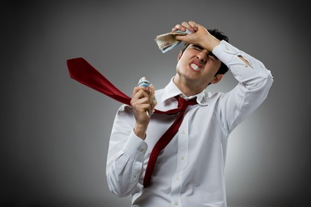 Desperate young businessman with blowing necktie and his bunch of money. Recession and crisis concept! photo