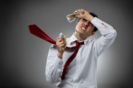 banconote euro: Disperata giovane imprenditore con soffia la cravatta e suo mucchio di soldi. Concetto di recessione e crisi!