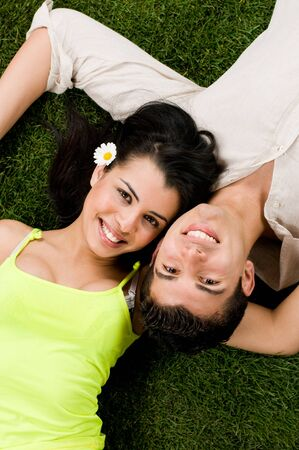 Young couple in love lying in a meadow while looking at camera photo
