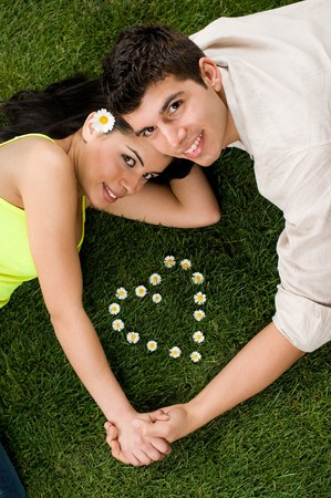 green dates: Young couple in love lying in a meadow while looking at camera, heart shape of daisy in the grass Stock Photo