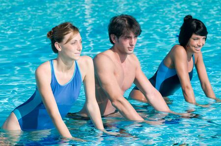 Happy young fitness people exercising with acqua bike in a swimming pool photo