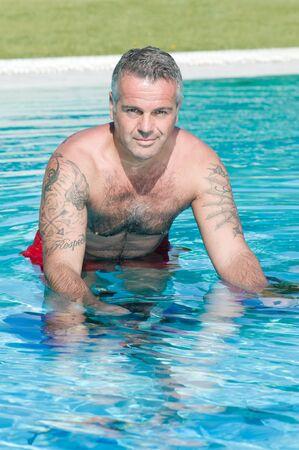 Homme mature sain exercice avec aqua vélo dans une piscine