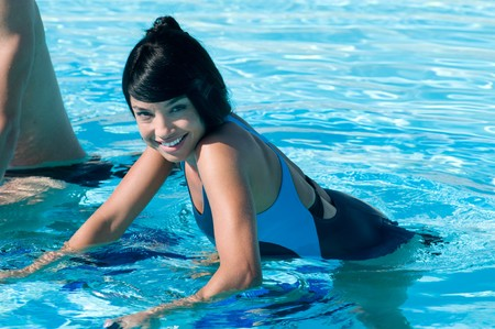 Happy smiling beautiful latin girl exercising with water aqua bike in a swimming pool photo