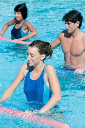 water aerobics: Active fitness people doing exercise with aqua tube in a swimming pool