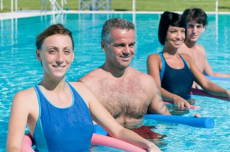 Happy active people exercising with aqua tube in water swimming pool photo