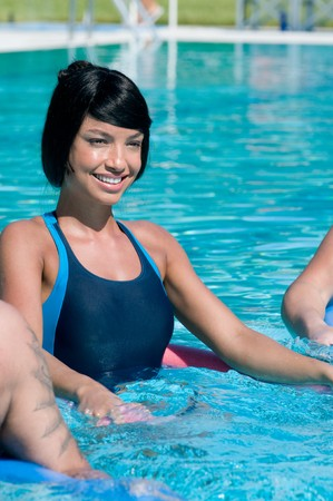 water aerobics: Young beautiful latin woman doing aqua gym exercise in a swimming pool
