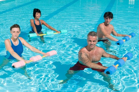 water aerobics: Happy active fitness people doing exercise with aqua dumbbell in a swimming pool