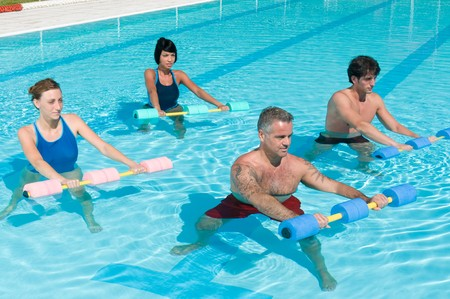 Group of healthy people doing aqua gym exercise with water dumbbell in a swimming pool photo