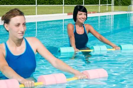 water aerobics: Two young girl doing aqua gym exercise with water dumbbell in a swimming pool Stock Photo