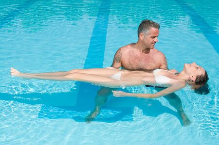 woman floating: Personal trainer give first lesson of swimming to a young lady in a swimming pool