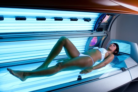 Young beautiful latin lady lying on a tanning bed at health spa photo