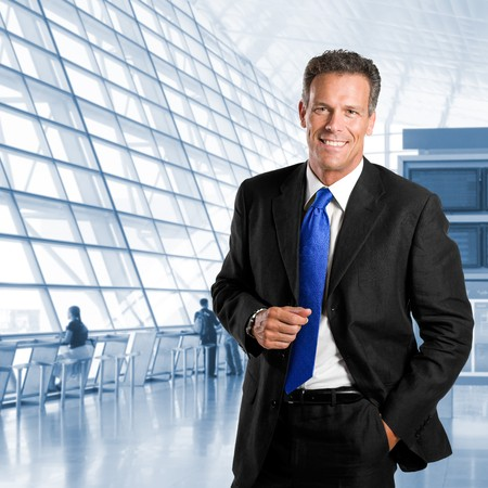 Mature successful businessman smiling and looking at camera in a modern office building