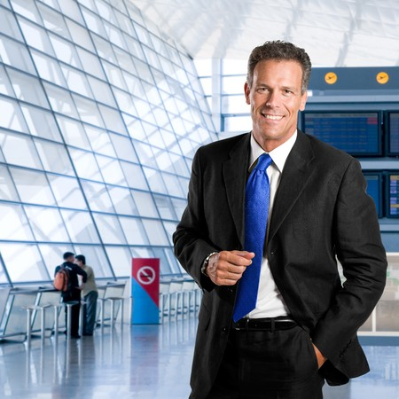 Mature successful businessman smiling and looking at camera in a modern airport photo