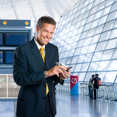 sms text: Mature successful businessman text messaging on mobile at the airport