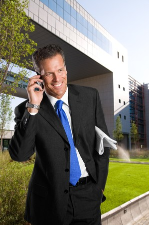 Mature successful businesssman talking on mobile outdoor in a business park Stock Photo - 8235329