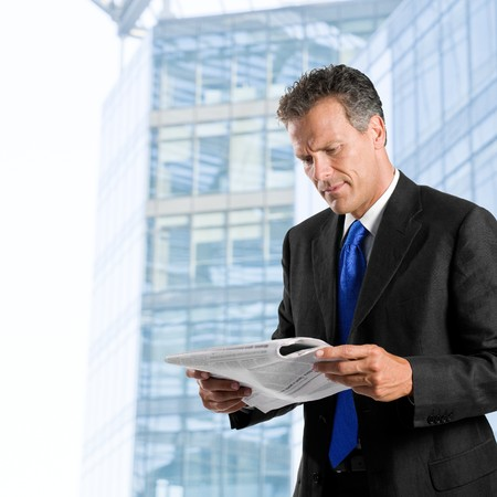 Businessman reading morning news standing against his modern building exterior photo