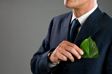 Stylish businessman holding a fresh green leaf in his pocket. Green business concept, take care of the environment! photo