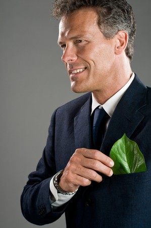 Mature businessman hold a green leaf in his suit pocket. Green business concept, take care of the environment! photo