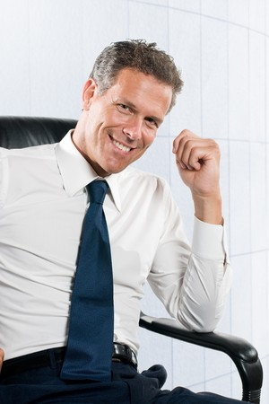 Smiling satisfied businessman looking at camera sit in his chair at office Stock Photo - 8235308