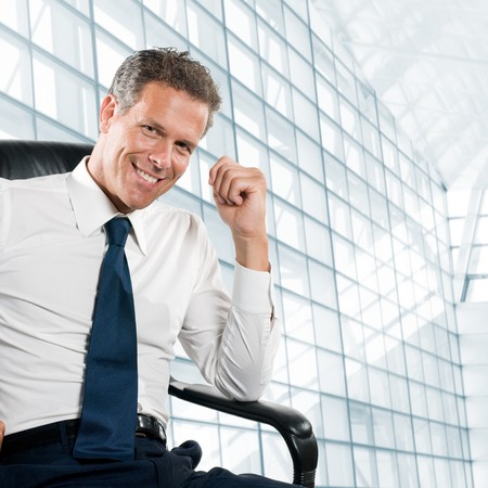 ceo: Smiling satisfied businessman looking at camera sit in his chair at office