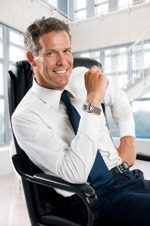 Smiling satisfied businessman looking at camera sit in his chair at office Stock Photo - 8235247
