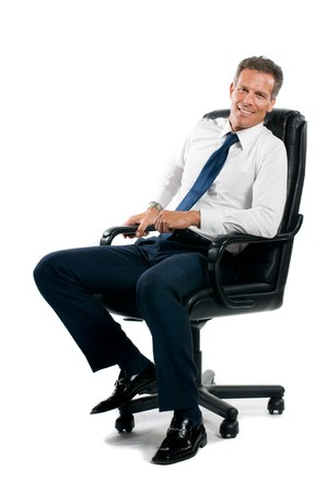 Smiling confident businessman sitting on chair and looking at camera isolated on white background photo