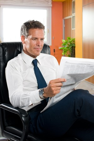 adult magazine: Businessman reading news while taking a break in his office