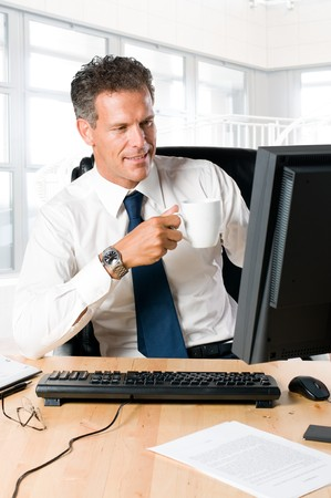 Succesful businessman sit at his desk while drinking a mug of coffee Stock Photo - 8235269